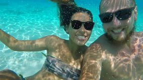 Young Happy Couple in Sunglasses Making Underwater Selfie with GoPro Camera. HD Slow Motion. Thailand. Young Happy Couple in Sunglasses Making Underwater Selfie stock video