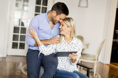 Young happy couple surfing on the web on tablet at home Royalty Free Stock Photography