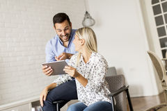 Young happy couple surfing on the web on tablet at home Royalty Free Stock Image