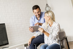 Young happy couple surfing on the web on tablet at home Stock Photos