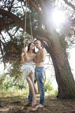 Young happy couple swinging Stock Images