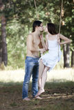 Young happy couple swinging Royalty Free Stock Photography