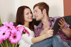 Young happy couple with tablet pc on the sofa Stock Photo