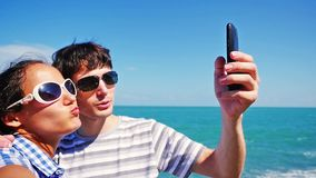 Pretty happy couple wearing sunglasses taking selfie at the beac with amazing sea view. Slow motion. 1920x1080 stock video