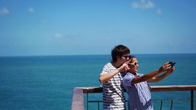 Young happy couple wearing sunglassrs taking selfie photo at the beach. Slow motion. 1920x1080 stock footage