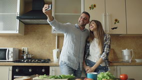 Young happy couple taking selfie picture while cooking breakfast in the kitchen at home stock video footage