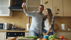 Young happy couple taking selfie picture while cooking breakfast in the kitchen at home. Early morning Royalty Free Stock Photo