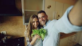 Young happy couple taking selfie picture while cooking breakfast in the kitchen at home. Early morning Stock Photos