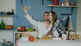 Young happy couple taking selfie portrait while having breakfast in the kitchen at home. At home early morning stock footage