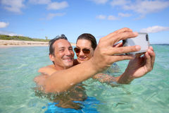 Young happy couple taking a selfie in the sea Royalty Free Stock Images