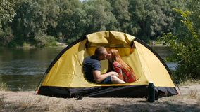 Young happy couple in the tent. Girl kisses a guy. They have a romantic moment. Forest and river on the background. Young happy couple in the tent. Girl kisses stock footage