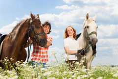 Young happy couple with their purebred horses Stock Photography