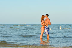 Young happy couple together on sandy beach embracing outdoors Royalty Free Stock Photography