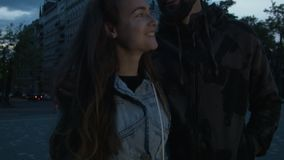 Young happy couple of tourists on the opposite night building smiling. Beautiful young man with a woman in the city. Twilight in the capital stock video