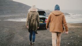 Young happy couple traveling by car. Attractive man and woman walking to the vehicle near the black beach in Iceland. stock footage