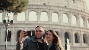 Young happy couple traveling in Rome, Italy. Man and woman taking the selfie photo on smartphone near the Colosseum. Young happy couple traveling in Rome, Italy stock photography