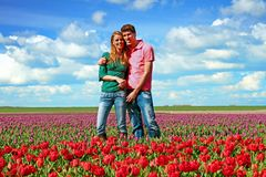 Young happy couple in the tulip fields from the Netherlands. Young happy couple in the tulip fields in the countryside from the Netherlands Royalty Free Stock Image