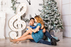 Young happy couple under christmas tree have fun at home Royalty Free Stock Photos