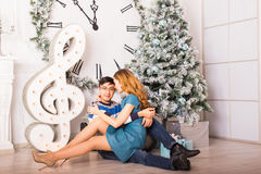 Young happy couple under christmas tree have fun at home Royalty Free Stock Photo