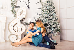 Young happy couple under christmas tree have fun at home Stock Images