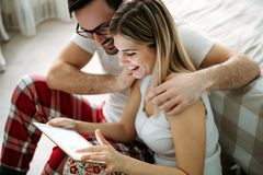 Young happy couple using tablet in bedroom Stock Images