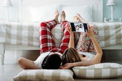 Young happy couple using tablet in bedroom Stock Photo