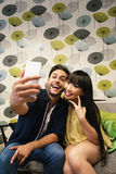 Young happy couple using smartphone in the bar Stock Images