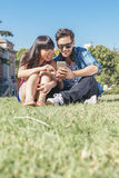 Young happy couple using smartphones in the park. Young happy couple using smartphones sitting in the park Stock Photo