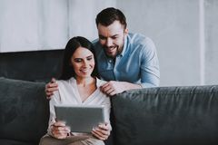 Young Happy Couple Using Tablet Device at Home. royalty free stock images