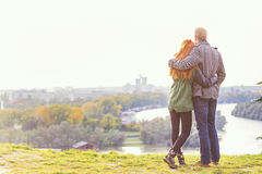Young happy couple ,view from behind, looking at city panorama. Stock Photos