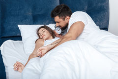 Young happy couple waking up with alarm clock in bed. Portrait of young happy couple waking up with alarm clock in bed Stock Photos