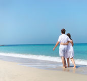 Young happy couple walking on the beach Stock Images