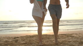 Young happy couple walking on the beach and holding hands of each other at sunset. Man and woman going on sea shore
