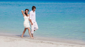 Young happy couple walking on beach shore Stock Photography