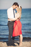 Young happy couple walking on beach smiling holding around each other. Love story Stock Photo