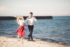 Young happy couple walking on beach smiling holding around each other. Love story Royalty Free Stock Photo
