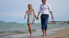 Young happy couple walking on beach smiling holding around each other. Romantic concept. HD, 1920x1080. Young happy couple walking on beach smiling holding stock video footage