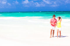 Young happy couple walking on beach smiling. Stock Photos