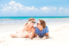 Young happy couple walking on beach smiling. Royalty Free Stock Images