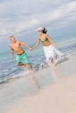 Young happy couple walking on beach sunset holiday Stock Photos