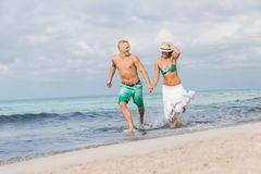 Young happy couple walking on beach sunset holiday Royalty Free Stock Image