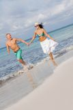 Young happy couple walking on beach sunset holiday Stock Image