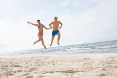 Young happy couple walking on beach sunset holiday Stock Images