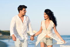 Young happy couple walking in a beautiful beach Royalty Free Stock Photography