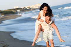 Young happy couple walking in a beautiful beach Stock Photo