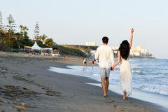 Young happy couple walking in a beautiful beach Royalty Free Stock Photos