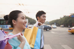 Young happy couple walking down the street with colorful shopping bags in Beijing Royalty Free Stock Photo