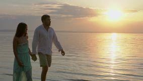 Young happy couple walking near the sea on the sunset. Concept of love. stock footage