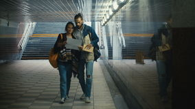 Young happy couple walking through the underground passage and looking on the map. Beautiful tourists in new city. stock video
