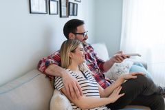 Young happy couple watching tv in living room royalty free stock photos